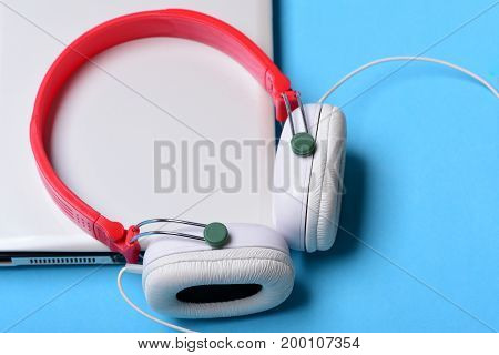 Headphones And Silver Laptop. Electronics On Blue Background, Top View