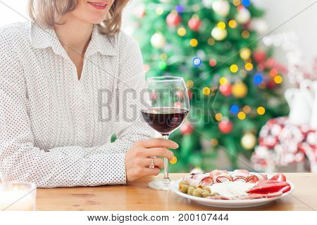 Young Woman, Drinking Wine And Having Snack At Home On Christmas