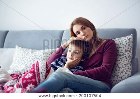 Young mother holding her little sick boy lying together on the couch