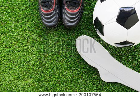 Soccer concept : Football (soccer ball) old soccer boots socks on green grass background. Flat lay with copy space.