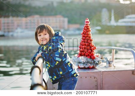 Cute Happy Child, Traveling On A Boat On A Lake During Christmas