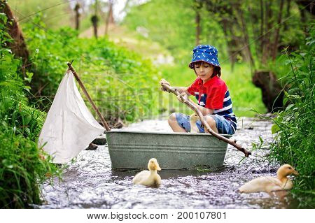 Cute Child, Boy, Playing With Boat And Ducks On A Little River