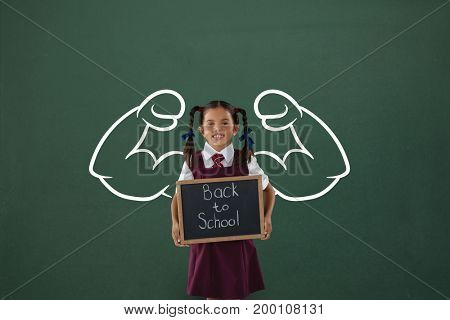 Digital composite of Happy student girl with fists graphic holding a little blackboard against green blackboard