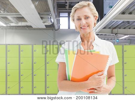 Digital composite of mature female student holding book in front of lockers