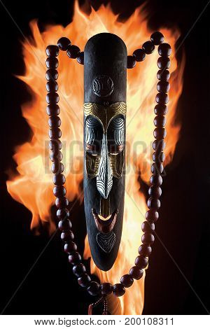 Photo of an ancient wooden mask with beads against fire flames.