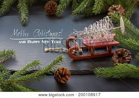 Christmas concept with red sleigh pine cones and fir tree branch on black background. Top view and copy space.