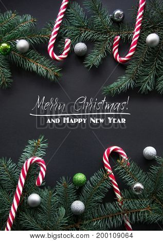 Christmas or New Year decoration background. Fir tree branches spruce candy colorful balls on black background with copy space. Top view.
