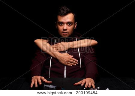 A close-up picture of a guy with a drug addiction on a black background. Drug-dependent with a syringe. Liquid ecstasy in a syringe. Young man in a wine colored jacket. Drug concept. Copy space.