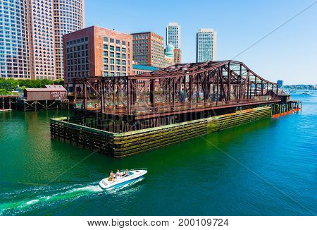 Boston - June 2016, MA, USA: Boat with people is floating on water from Boston harbor towards the open sea (ocean)