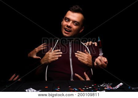 A crazy, obsessed junkie having drug hallucinations, sitting near many narcotics on the table. An expressive and problematic male looking at the drug syringe on a black background.