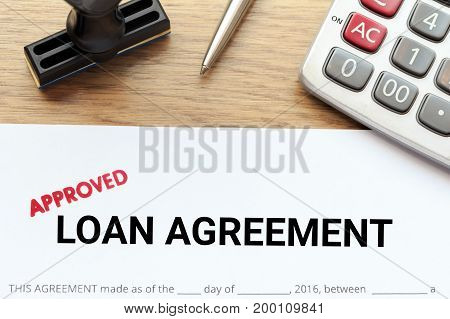 Approved loan agreement document with rubber stamp and calculator on wooden desk