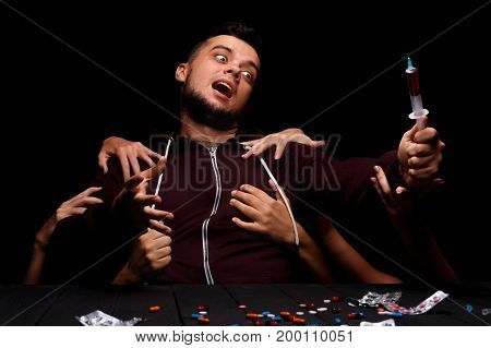 A suicidal, stressed student reaching to a drug syringe on the black background. Hands tearing apart a young man from the dark abyss. Youth addicted to abusive drugs. Conceptual social photography.