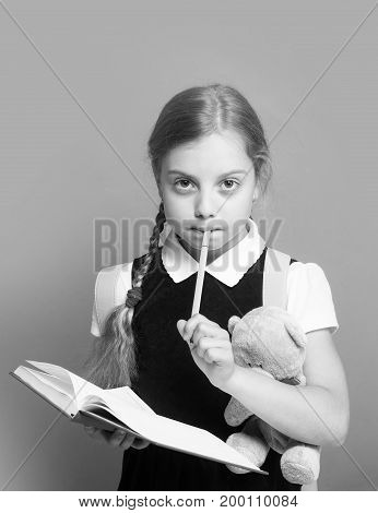 Study and back to school concept. Kid in school uniform isolated on green background. Pupil holds blue book marker and teddy bear. Girl with braids and thoughtful face expression