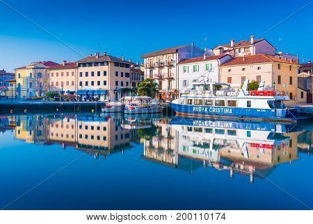 Grado - December 2015, Friuli Venezia Giulia region, Italy: Colored residential buildings and boats are mirror reflected in sea water