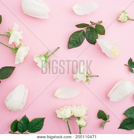 Pattern of white roses, tulips and leaves on pink background. Flat lay, top view. Floral concept.