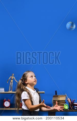 Girl In Classroom With Colorful Stationery And Books