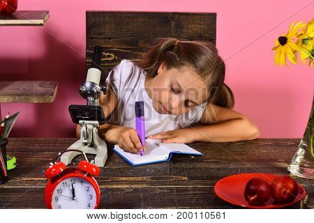 Girl Sits At Her Desk With Clock, Microscope And Fruit