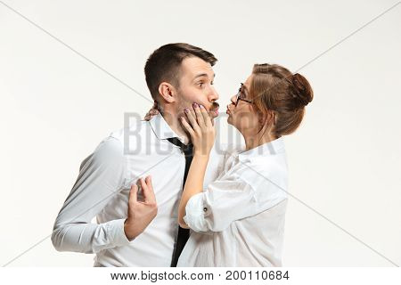 The surprised emotional business man and woman communicating on a gray studio background. The Flirtation and love concept