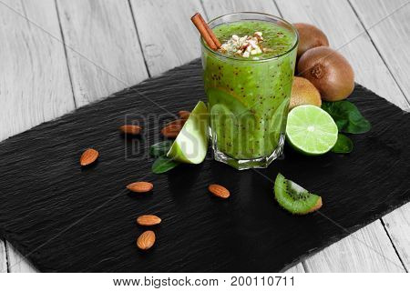 A thick, blended kiwi milkshake with juicy limes and cut apples on a black tray. A fresh non-alcoholic beverage with spices and nuts on the wooden table background. Pretty natural composition.