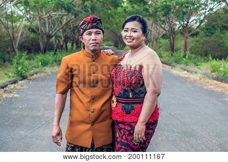 Lovely Honeymoon Balinese Couple In Traditional Clothes Together In Nature. Bali Island, Indonesia.