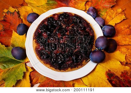 Homemade plum cake and autumn leaves. Top view