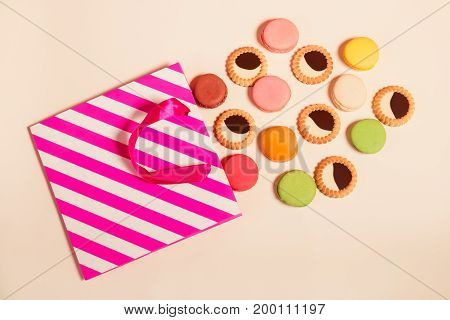 Paper bag with biscuits macaroon and cookies with chocolate. Top view