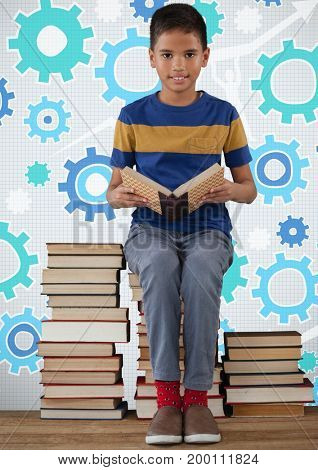 Digital composite of Boy reading and sitting on book tower in front of cog gear settings