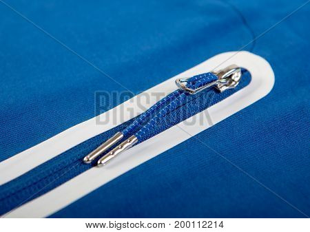 Metal zip closure sports a blue jacket or sweatshirt with pockets and white stripes close-up