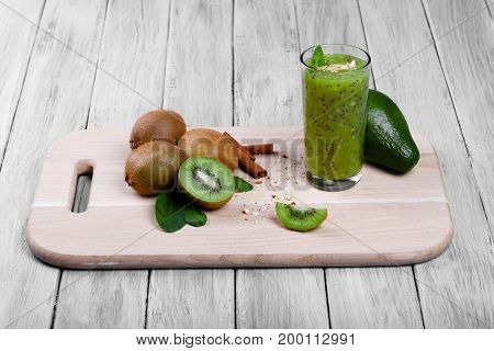 Sweet summer green kiwi drink or smoothie from exotic kiwi fruits, avocado, walnuts, cinnamon and mint on a gray wooden background, close-up. Cinnamon sticks, avocado, and kiwis on a desk.