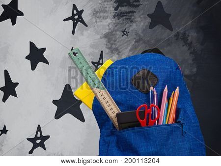 Digital composite of Schoolbag on Desk foreground with blackboard graphics of stars