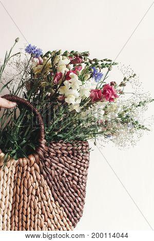 Hand Holding Wildflowers In Wicker Bag At Rustic Window. Colorful Flowers In Brown Basket In Sunligh