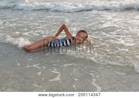 A young girl rejoices the summer and the warm waves of the Gulf of Mexico, Florida, USA