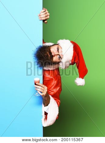 handsome bearded santa claus man with long beard on serious face holding glass of alcoholic shot in red christmas or xmas coat and new year hat on colorful studio background