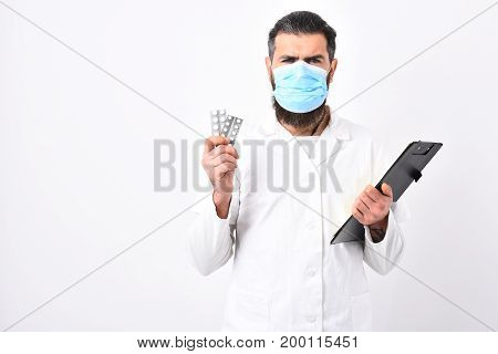 Medical Doctor With Stylish Haircut Holding Black Folder And Pills.