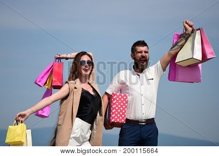 Man With Beard And Long Haired Woman Hold Shopping Bags