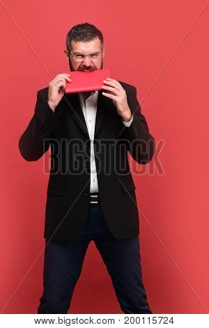 Success business and studying concept. Guy bites closed notebook. Businessman with busy face and glasses on light red background. Man in classic outfit with beard holds red organizer in teeth