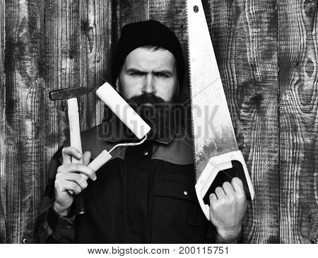 bearded man long beard brutal caucasian hipster with moustache holding various building tools: saw hammer roller paint with serious face on brown wooden studio background