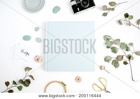 Blue family or wedding photo album with blank space for text eucalyptus leaf retro camera and dry rose buds on white background. Flat lay top view.
