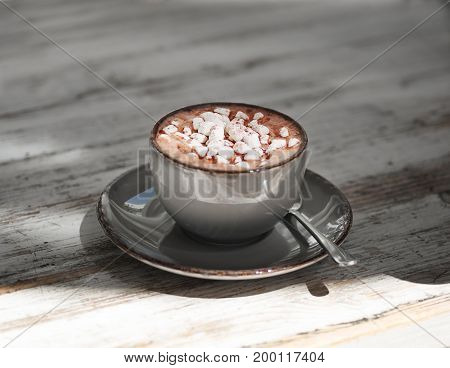 Tasty cappuccino on a gray wooden table background. A macro picture of a gray porcelain mug full of sweet cacao drink with white marshmallows. A cup with a metal spoon. Breakfast concept.