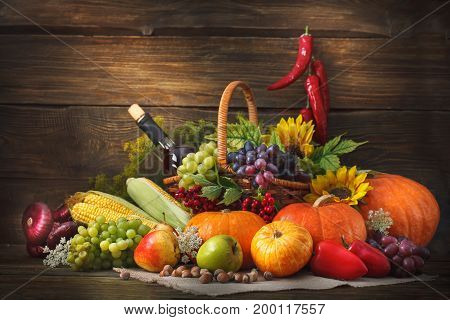 Happy Thanksgiving Day background, wooden table, decorated with vegetables, fruits and a bottle of wine. Autumn harvest festival.