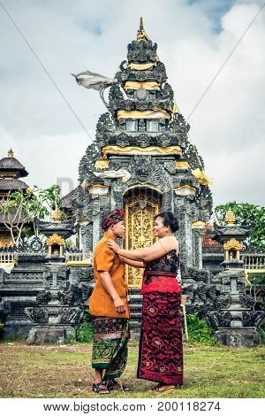 Lovely Honeymoon Balinese Couple In Traditional Clothes Together At The Balinese Temple. Bali Island