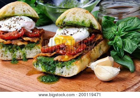 Toasted ciabatta with pesto slices of bacon sun-dried tomatoes and poached egg