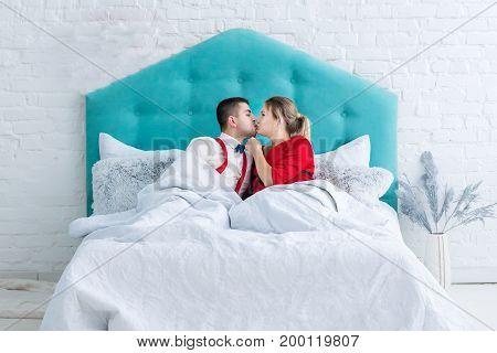 Young adult heterosexual couple lying on bed and kissing. Studio shoot