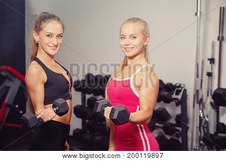 Close-up two girls smiling holding dumbbells in their hands and performing an exercise on the biceps, bending the arms at the elbow. Concept group sports with a friend.