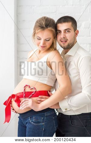 Man and pregnant woman with belly. Red and white heart made of candy on pregnant belly. Pregnant belly dressed with a red festive ribbon