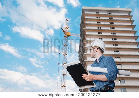 Male construction builder worker - foreman is engineer in protective helmet,glasses on the background of building a house with a crane. Concept calculation construction time, cost.