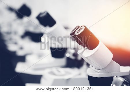 A row of microscopes stands in a room background. Concept medicine, biology, research, education. With a glare of sunlight