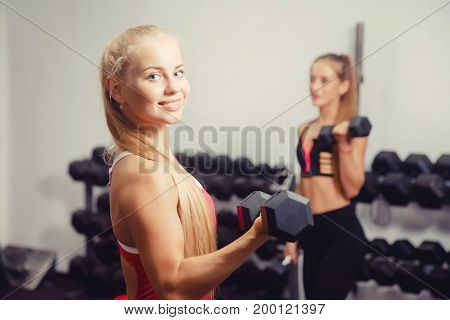 Woman exercising with a dumbbell in the gym, biceps exercising close-up, smiling in frame, camera, in the background a girl trains. copyspace