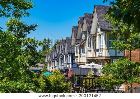 Perspective look at row of new townhouses surrounded by tree's leaves