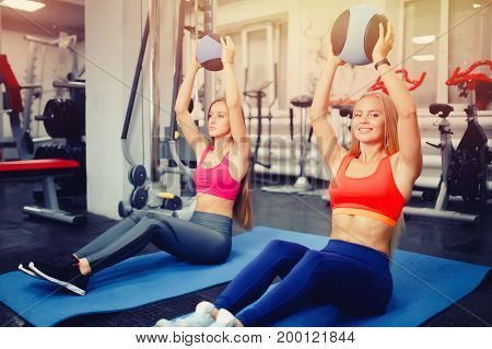 Young girl exercise with medical ball In fitness club. Concept teamwork aerobics, fitness, coach with a student. light